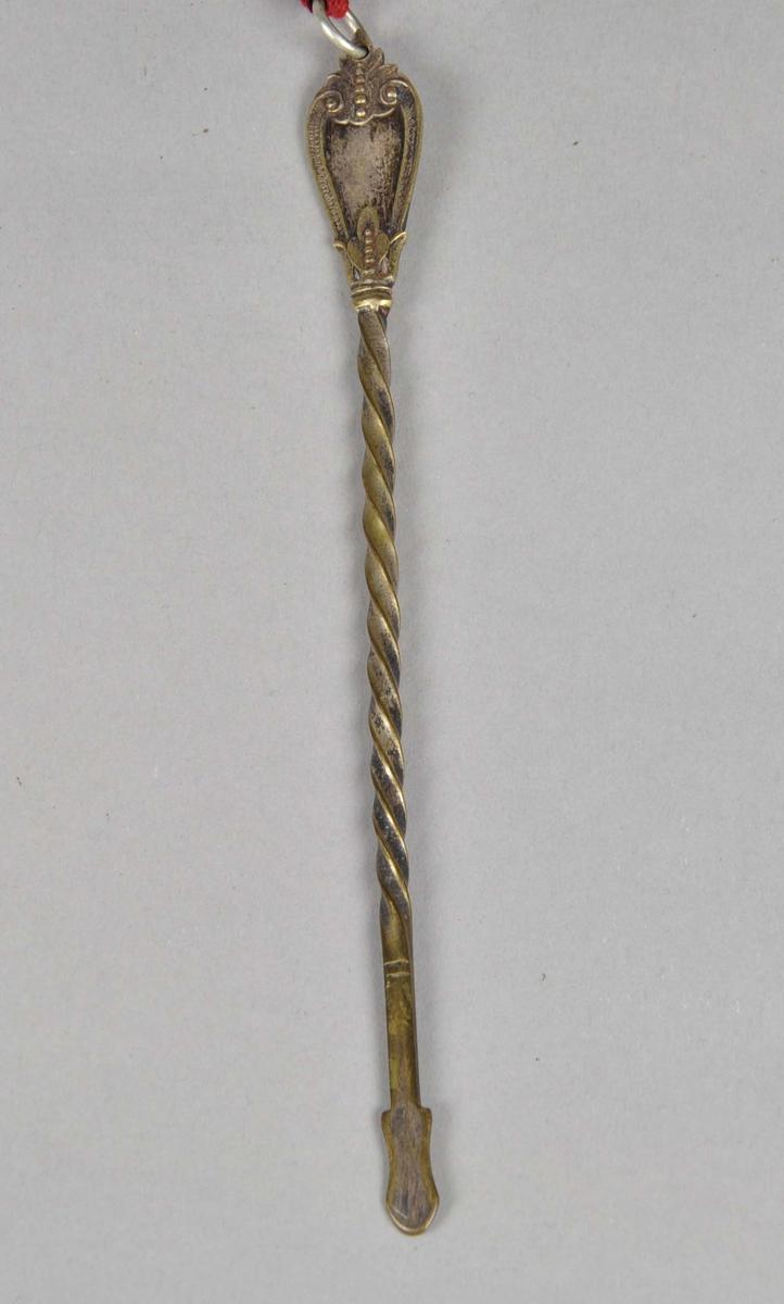 Tvunnet sølvpinne som smalner og er flat i nederste kanten med feste for et tekstilbånd. Båndet er brodert med ullgarn med halve korssting i mange farger, kantet med en tvunnet snor, fôret med linstoff og har en rød silkesløyfe øverst.