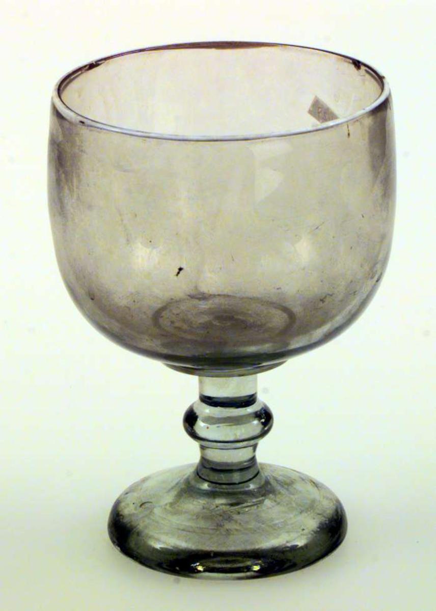 Pokalen er av glass. Den har form som et stort stettbeger. Den er ikke dekorert. Den har hvit munningsrand.