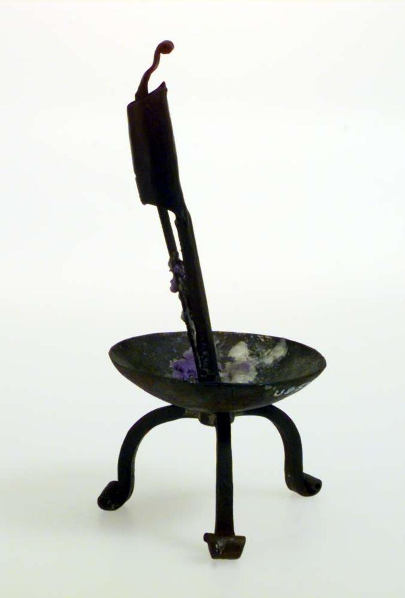 Lysestake av jern. Den står på tre føtter og har en vid 'dryppskål'. Den har en klemmemekanisme for å holde lyset på plass.