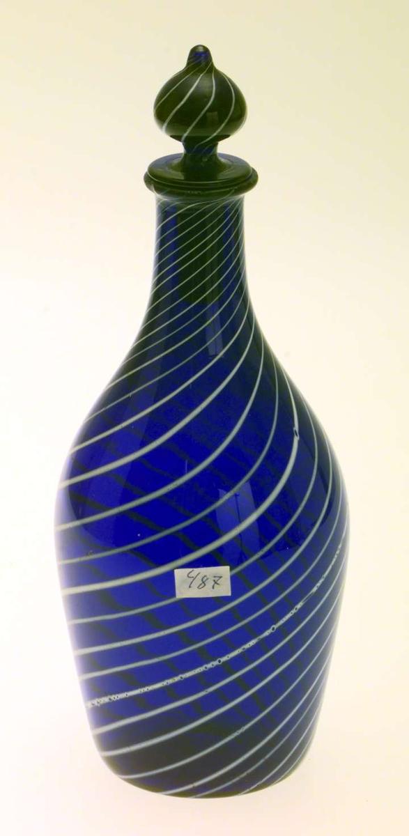 Karaffelen er av blått glass med hvite emaljestriper. Den har rundt tverrsnitt med buket korpus og smal hals. Den har propp. På proppen er det risset inn tallet 1960. Proppen er ikke original.