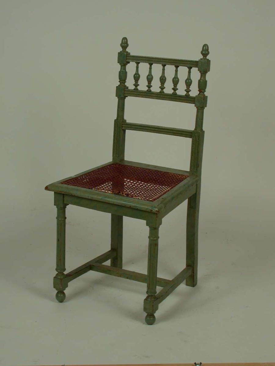 Lasert grønn stol. Setet er av rotting. Rottingen har røket. Stolen er laget i en blanding av stilarter.
