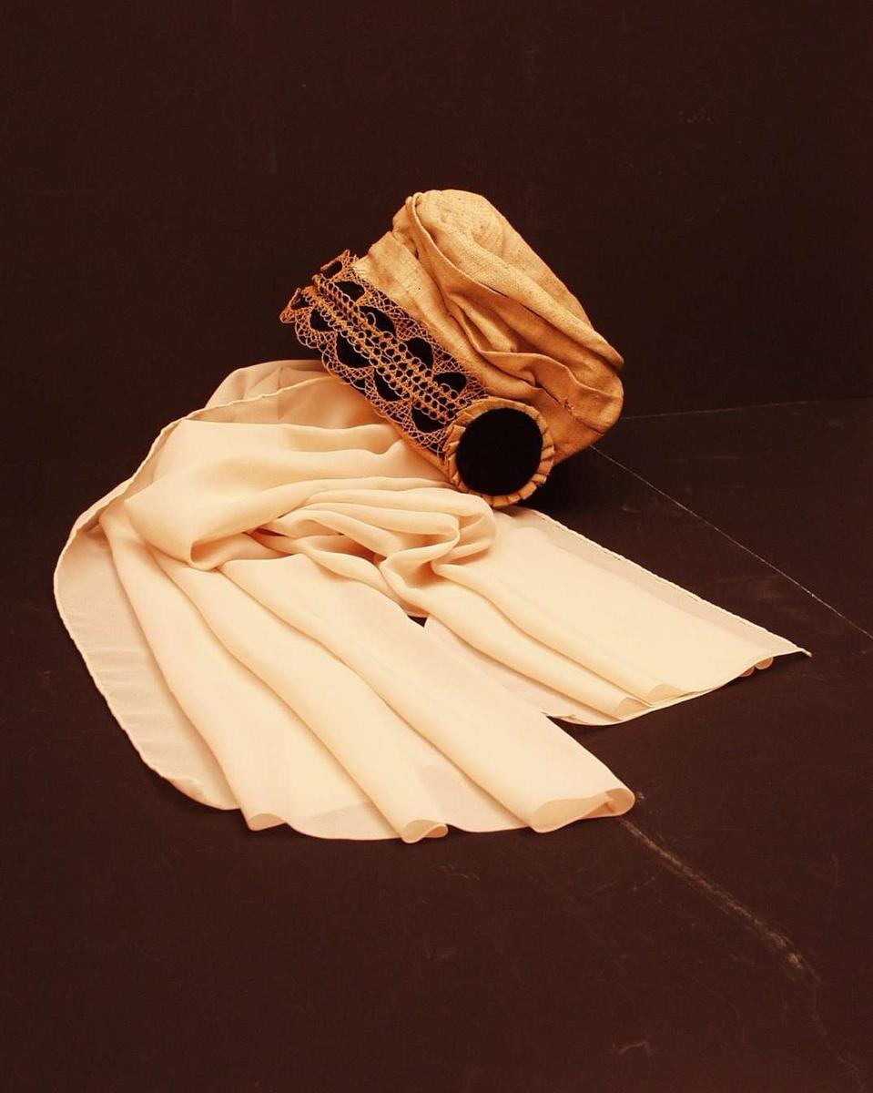 Ecrufarget kysehatt i bast med pyntebånd på kysekanten og rosetter ved ørene i sort fløyel. Kysen har lange, skjerflignende knytebånd i georgette.