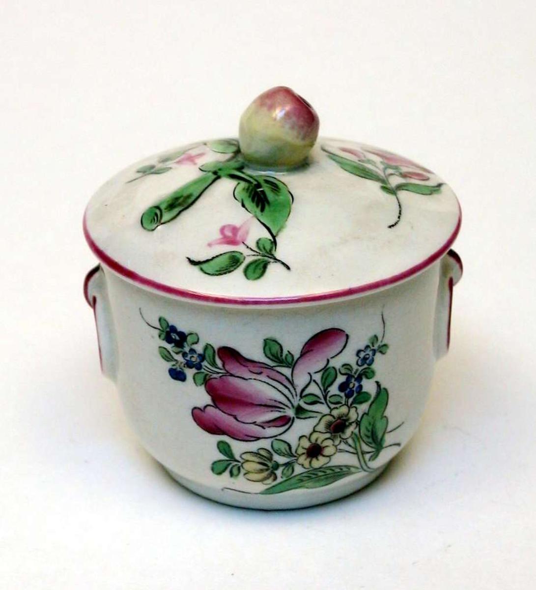 Krukke med lokk i kremfarget keramikk og med blomsterdekor. Den er stemplet Demi-porcelaine, Luneville, France, med bokstavene K og G rundt en krone.