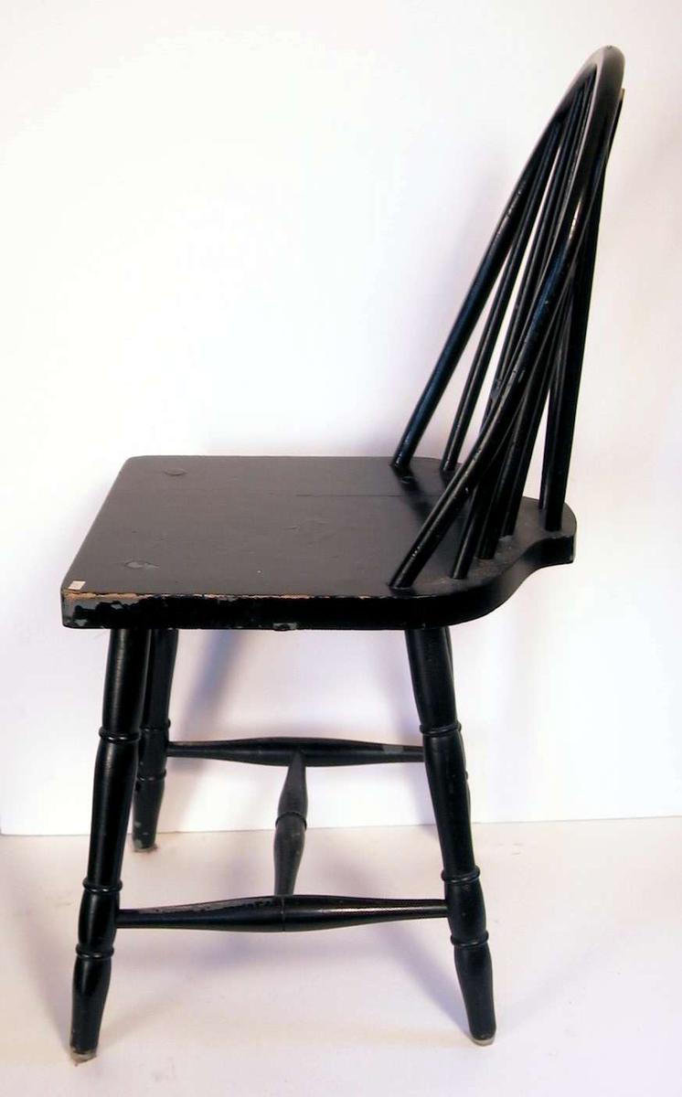 Sortmalt pinnestol med sprosser i ryggen.