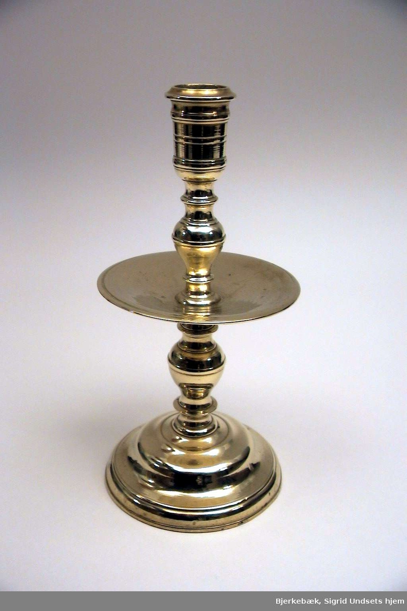 Lysestake av messing på rund fot med dryppskålen midt på staken. Dryppskålen har samme diameter som foten.