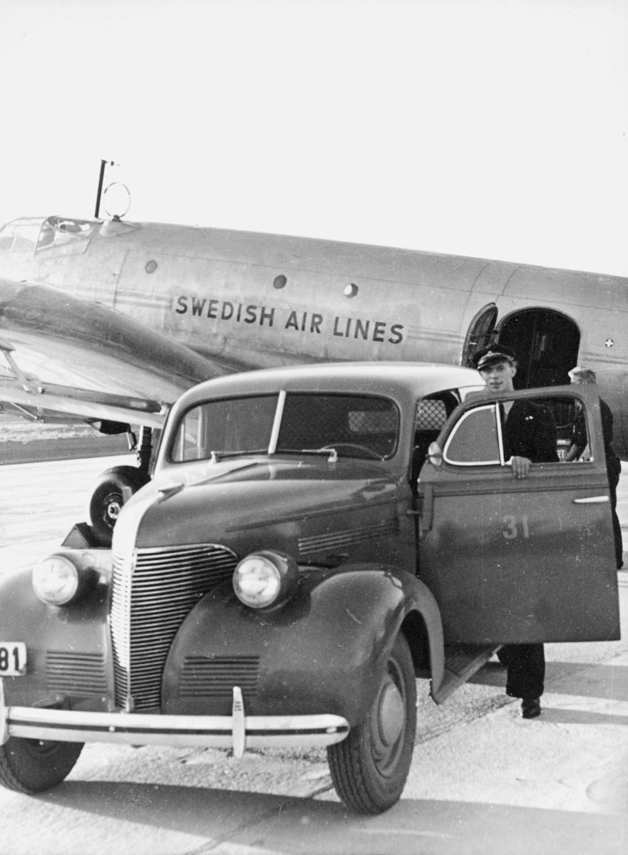 """transport, fly, Junkers Ju86 Z-7 SE-BAE, """"Svalan"""",  eksteriør, Fornebu, Swedish Air Lines, bil, mann. Chevrolet varebil, årsmodell 1939."""