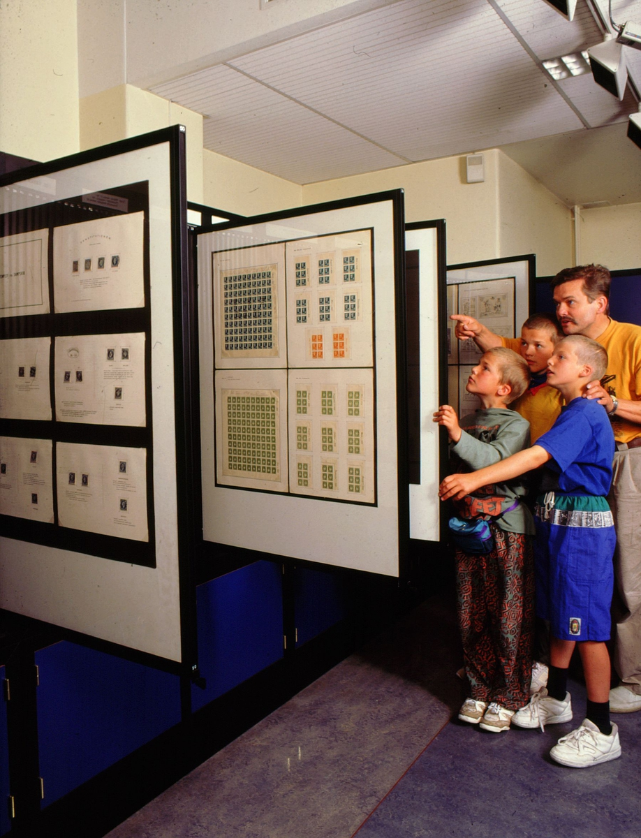 postmuseet, Kirkegata 20, utstilling, frimerker, frimerkerammer, 3 barn og mann ser på frimerker