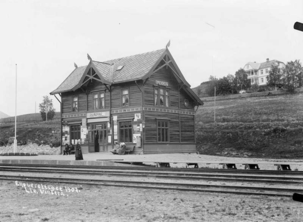 Kort: Sør- Fron, Hundorp jernbanestasjon.16.06.1907. Bygning, jernbaneskinner, reisende, villa i bakgrunnen.