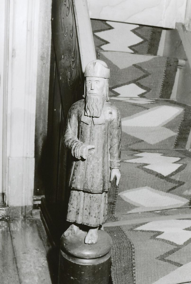 Menneskefigur: Mann m. skjegg, langt hår, frontal, v.arm på magen, kjortel, kofte, lue, drakt: brun m. blomster.
