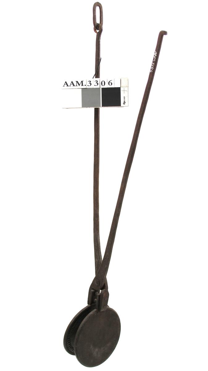 Krumkakejern  Sirkelrundt   støpejern  stekehode med innvendig dekor  i form av rosett omgitt av tunget bord.  Smijern håndtak holdt sammen ytterst av bøyle.  Ett av håndtakene festet med nye nagler.  Tilstand juni 1963: god, litt rustanløpet.
