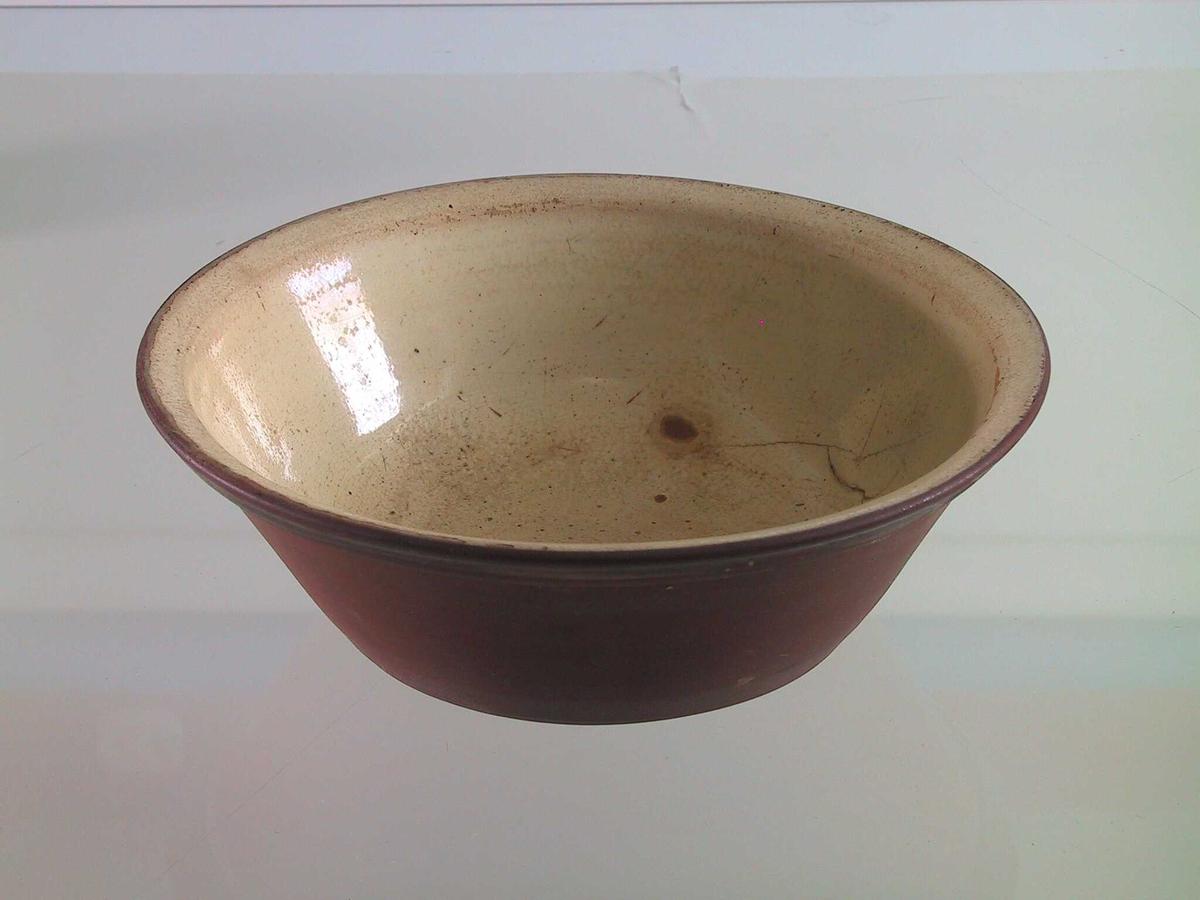 Smal ut brem, lite markert på innsiden. Oval brun flekk uten glassur  i overgang bunn/side.