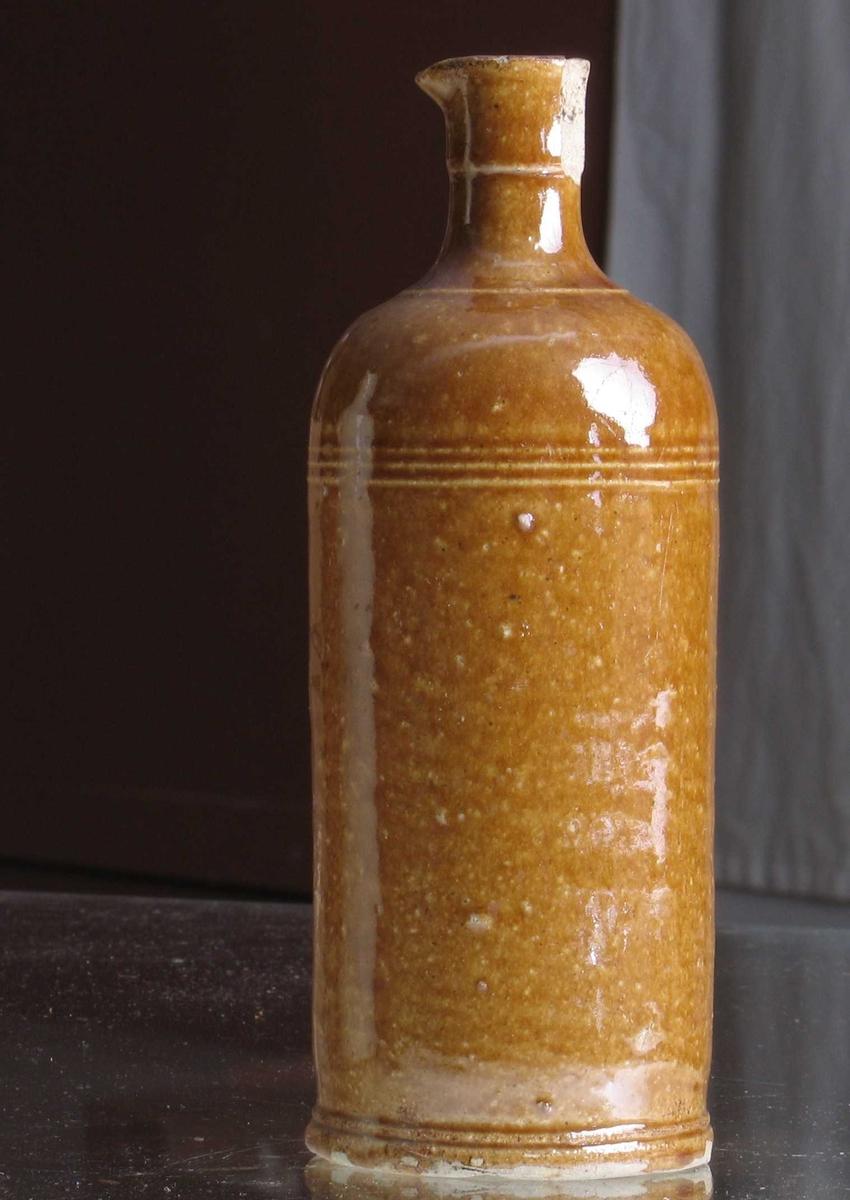 """Flaske med tusj,  innstemplet nede.  l """"Rhinsk""""""""stentøytype, grågult gods med avskjærings tiller  i bunnen, brunglassert.  Sylindrisk flaske med rin er nede  og øverst mot de runde skuldre.  Brem med tut. Et stykke av bremmen slått av."""