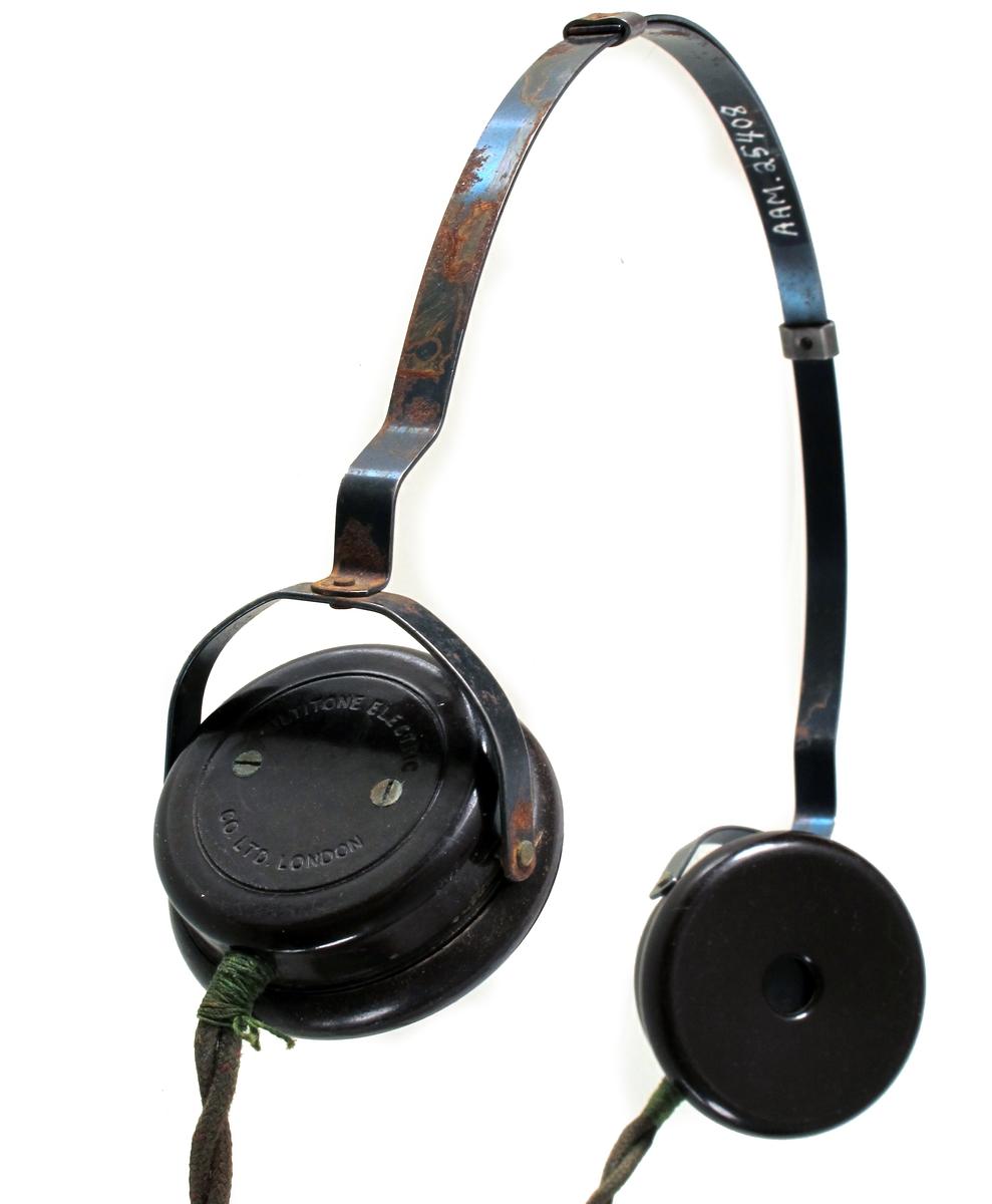 """To runde øretelefoner montert på bøyle, ledning. Hørte til radio som ble brukt til illegal lytting av """"gutta på skauen"""" når de lå og ventet på slipp."""