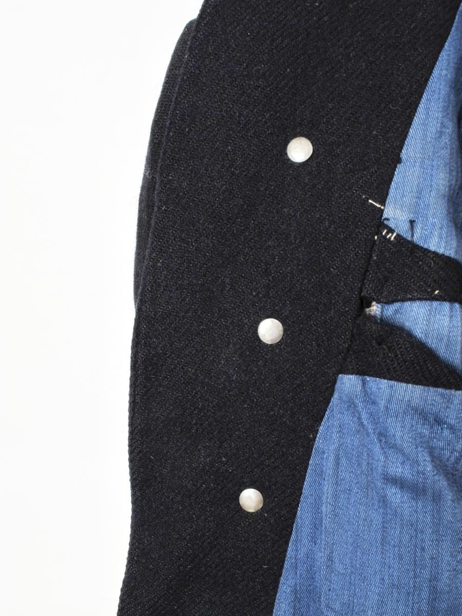 Jakke, fangejakke m.fangenummer, enkeltspent. Ultramarin farge.  Maskinsydd. Ull i jakken, bomull i foret.   Stempel er på knappene. Tallet 17635 er fangenummer. Det er malt med sjablong på et stykke hvitt bomullslerret, sydd på høyre bryst. Tallet 51 er størrelse.