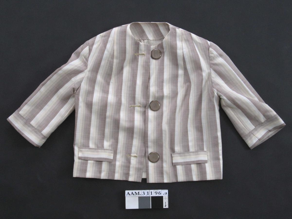 Rett jakke, rund halsringning, 3/4 ermer med mansjett, 3 store knapper foran. Jukselommer ved hofter.