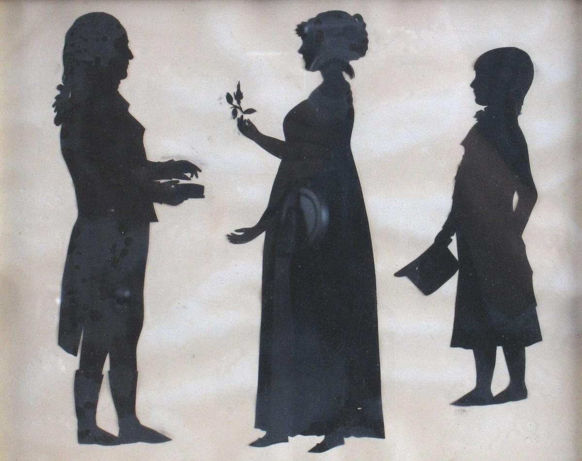 """3 personer, stående, helfigur. Silhuett av Peter Andreas Hiorth, 1740 -1817,  (generalmajor, yngste sønn av magister Peder Hiorth og Anna Andersd. Dedekam) med ektefelle (gift 1770)  Birgitte Christine Werner, 1751- 1813, og sønn Peter Andreas Hiorth, 1771 1811, infanterikaptein,  Nannestad.   T.v. general Hiorth prof. h, i piskeparykk, langskjøtet frakk  m. høy krave og brede slag, trange bukser og høye støvler  (""""Wertherdrakt""""), står m. snusdåse i hånden.  Vendt mot ham, profil v, fru Hiorth, i hånden holder hun  en rosenknopp, iført vid empirekjole m. høyt liv, flate tøysko,  kappe eller høy frisyre på hodet. Helt t. h. m/ profil v.,  sønnen, en halvvoksen gutt: i sid frakk, m. halsbind m. sløyfe, naturlig hår,  børstet frem i pannen, langt i nakken. Holder en  kort, høy stiv hatt i hånden."""