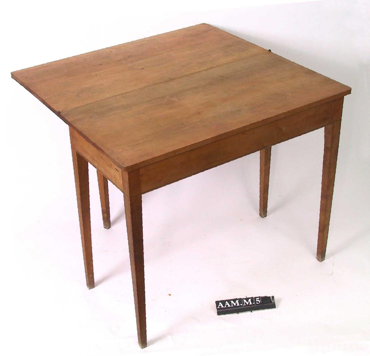 Spillebord, empire norsk  Bjerk. Rette ben, rett sarg uten skuff, med en  innlagt sort stripe nederst. Bordplate med en sort stripe rundt kanten når bordet er slått sammen.  Utslått er bordplaten firkantet og uten dekor. Ved venstre bakben et ekstra ben som kan slås ut.