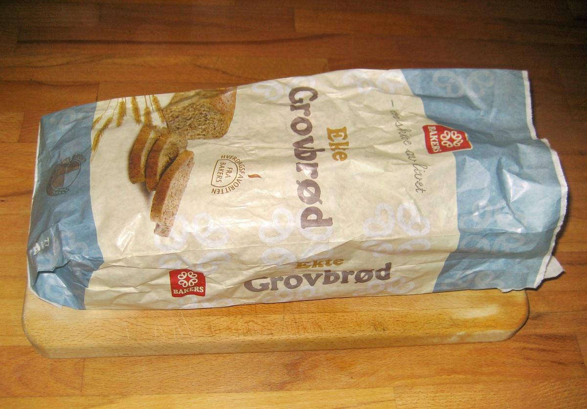 Motivet på brødposen et brød med tre oppskårne brødskiver og noen kornaks