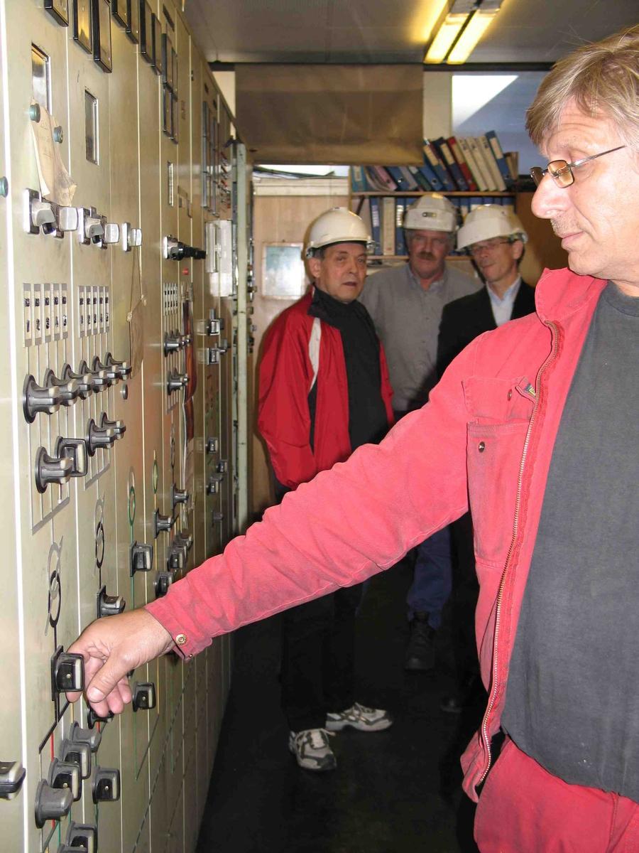 Strømmen slåes av for siste gang i kontrollrommet ved ovnshus B. Direktør, formann og fagforeningsleder i bakgrunnen.