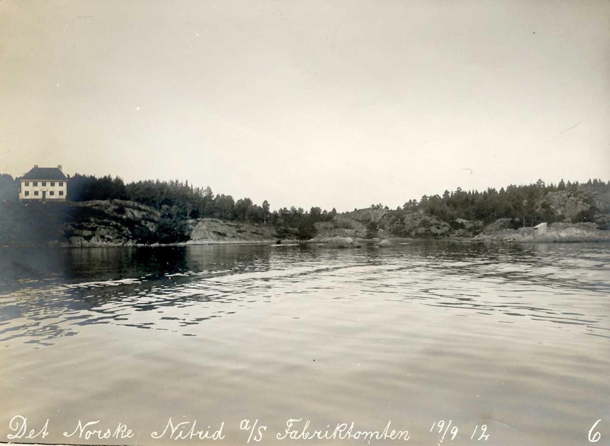 """""""19/09-1912"""" Nitriden. Smelteverkets direktørbolig til venstre. Terrenget til høyre er fabrikktomten til Nitriden. Kupert terreng. Tromøysund i forkant."""