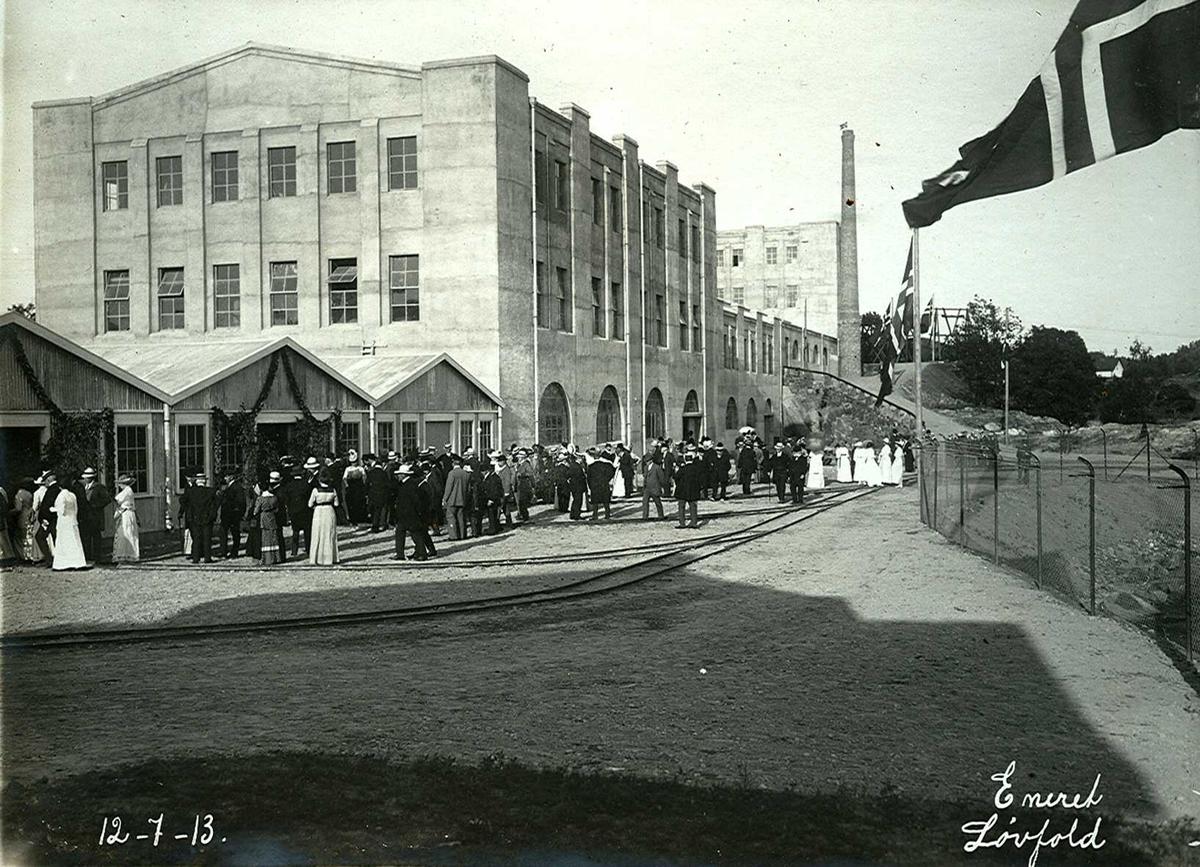 """""""12/07-1913"""" Smelteverket. Befaring av fabrikkanleggene i forbindelse med at stedet fikk navnet Eydehavn 12. juli 1913 og offisiell åpning av fabrikken. Det var pyntet med løvkranser og flagg. Etter """"dåpsseremonien"""" ble de besøkende ble vist rundt på det den gang ca. 5000 kvadratmeter store fabrikkanlegget. Bygningene i forgrunnen er Kjemisk vaskeri, og Pakkeri. Murbygningen er Mølle II (finknusing av produktet), deretter Ovnshus II, Rørovnshus med skorstein og Mølle I (grovknusing av råmaterialer)."""