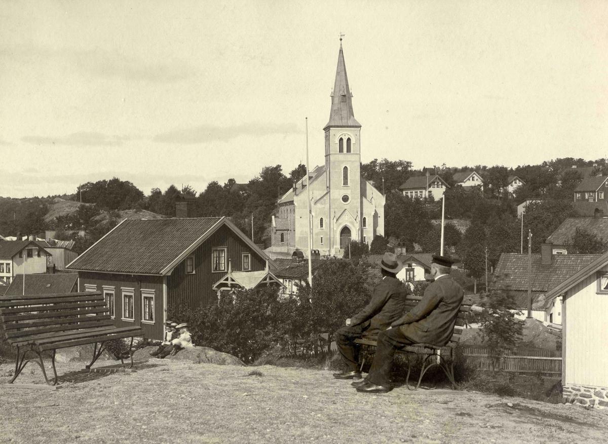 Kirke med omgivelser. Barbu kirke sett fra Margrethestiftelsen, eller Åsenparken som stedet kalles i dag. To menn sitter med ryggen til.  Stedsbilder Arendal Barbu kirke - nr 1177