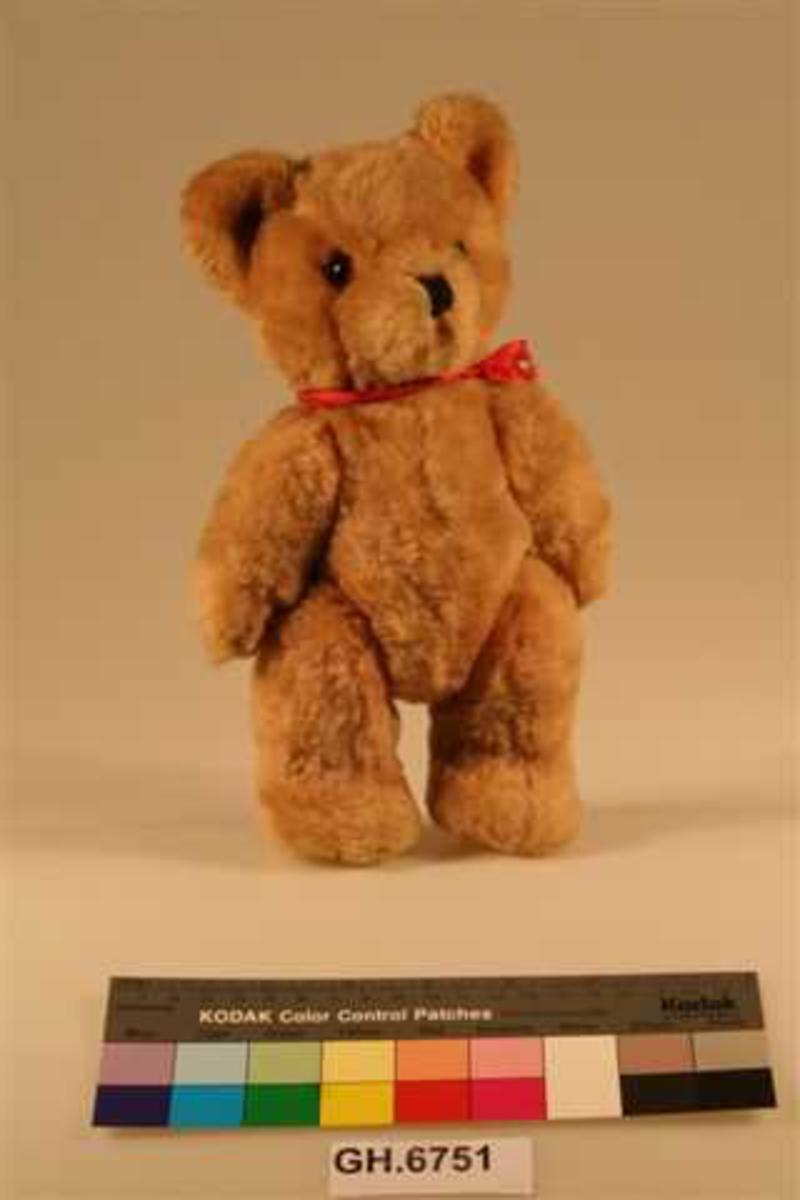Teddybjørn med bevegelige armer og ben. 2 avrundede ører som står rett opp. Øyne av glass. Nesetippen markert med mørk brunt stoff. Munn og poter markert med mørk tråd. Et rødt bånd er knyttet rundt halsen.