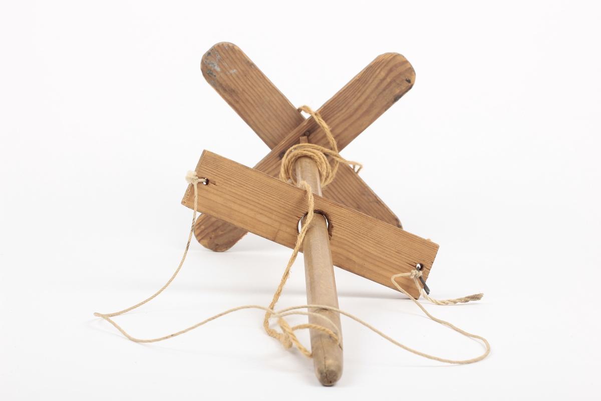 """Korset er spikret sammen med små spiker, festet til stolpen med trestikke over og under korset. Pinne festet til stolpen med hyssing. Ved å bevege pinnen opp og ned på stolpen, roterer stolpen og korset - hyssingen må da være snodd rundt stolpen. Gran i kors og pinne, lauvtre i stolpen. Tidl.reg.: Kalt Skottrokk: """" Laget av Chr. Braaten f. 1869 - Sløydlærer, sogneprest L? Hofgaard"""""""