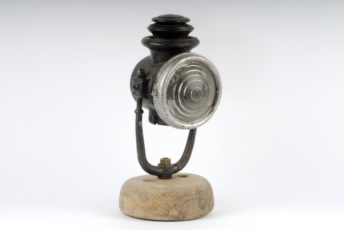 Form: Sylinderformet lykt med rundt glass i fronten. Stativ av jern satt ned i foten. Oljedrevet til lampe før 1914 i Tyskland