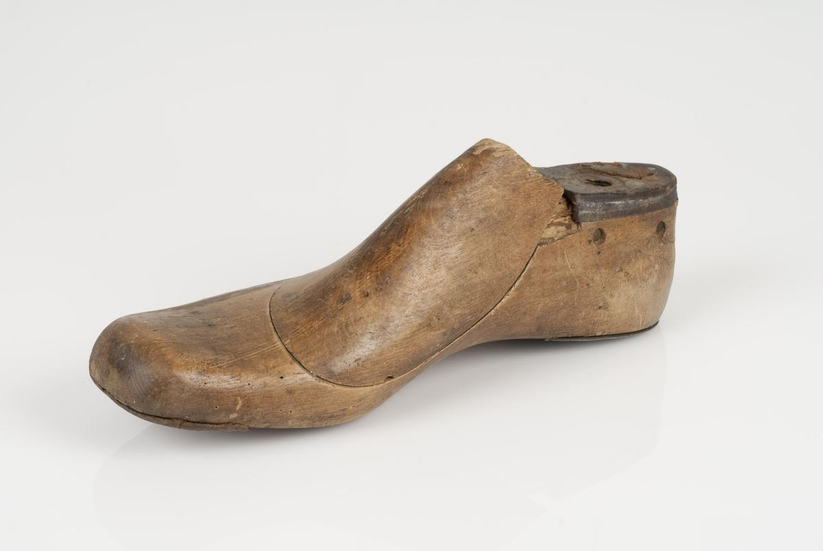 En tremodell i to deler; lest og opplest/overlest (kile). Høyrefot i skostørrelse 43, og 8 cm i vidde. Lestekam i skinn. Hælstykket i metall. Tåspringsåle i skinn.