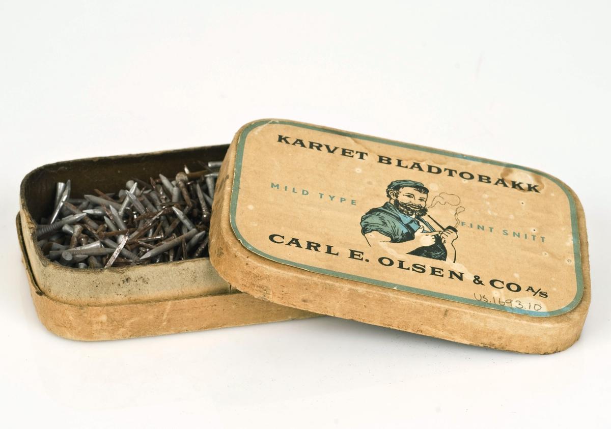 Forskjellige spiker av stål i en tobakkseske av papp.