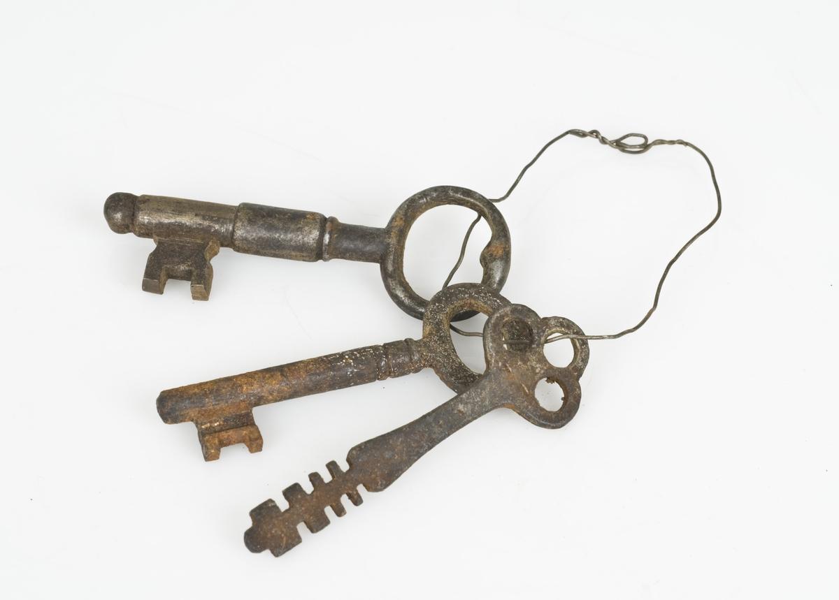 3 nøkler av jern. Nøklene henger sammen i en stålring.