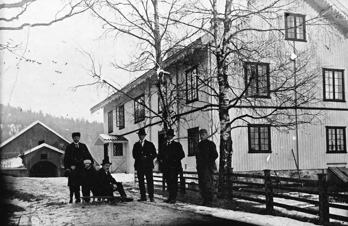 Krokhol gård hovedhus og låve. Fem voksne menn og to barn med kjelke oppstilt foran hagegjerdet.