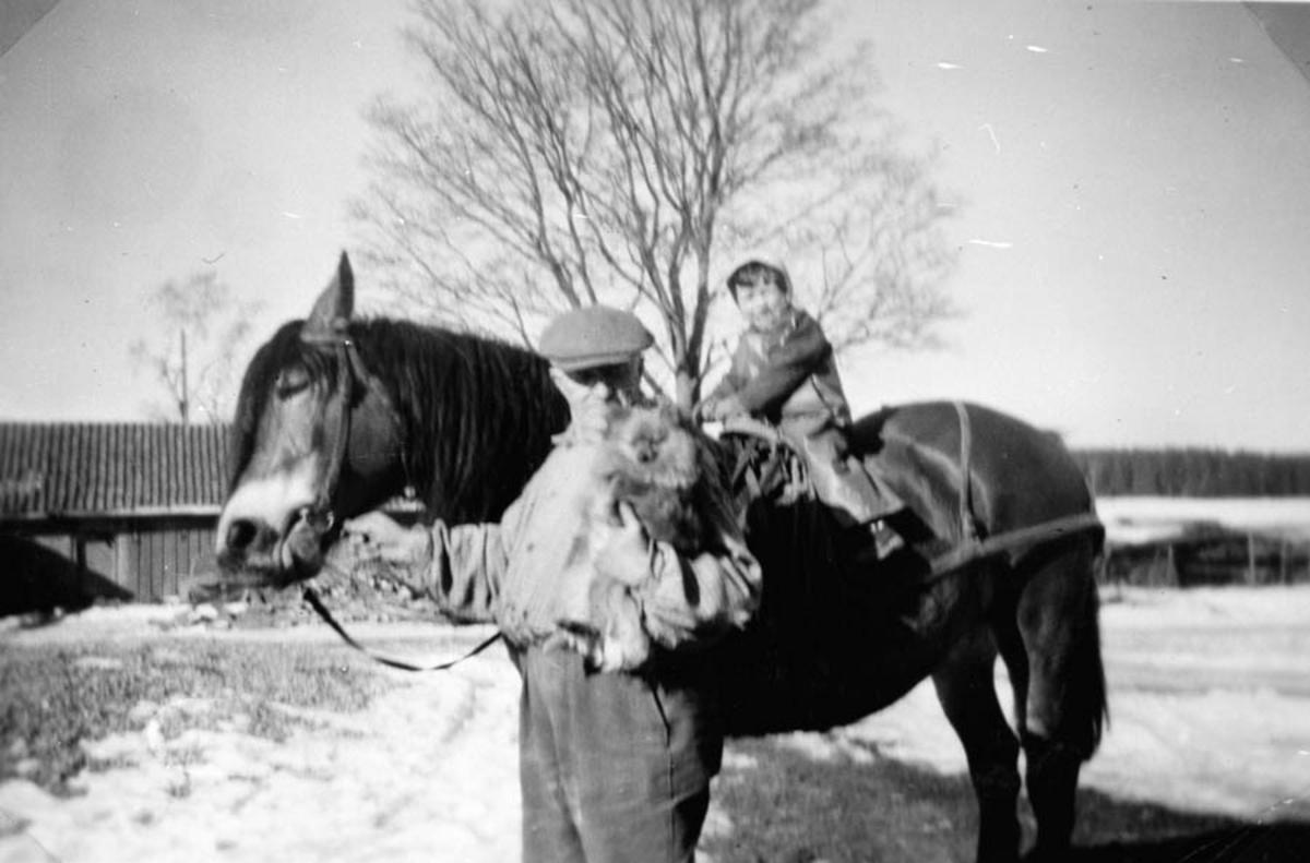 Mann med hest som har et barn på ryggen.