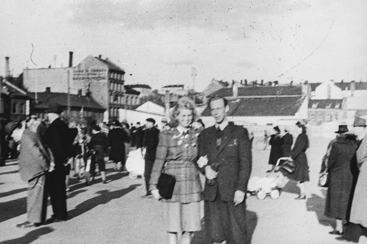 Et ungt par fotografert blant mange andre personer som er ute og feirer frigjøringen.
