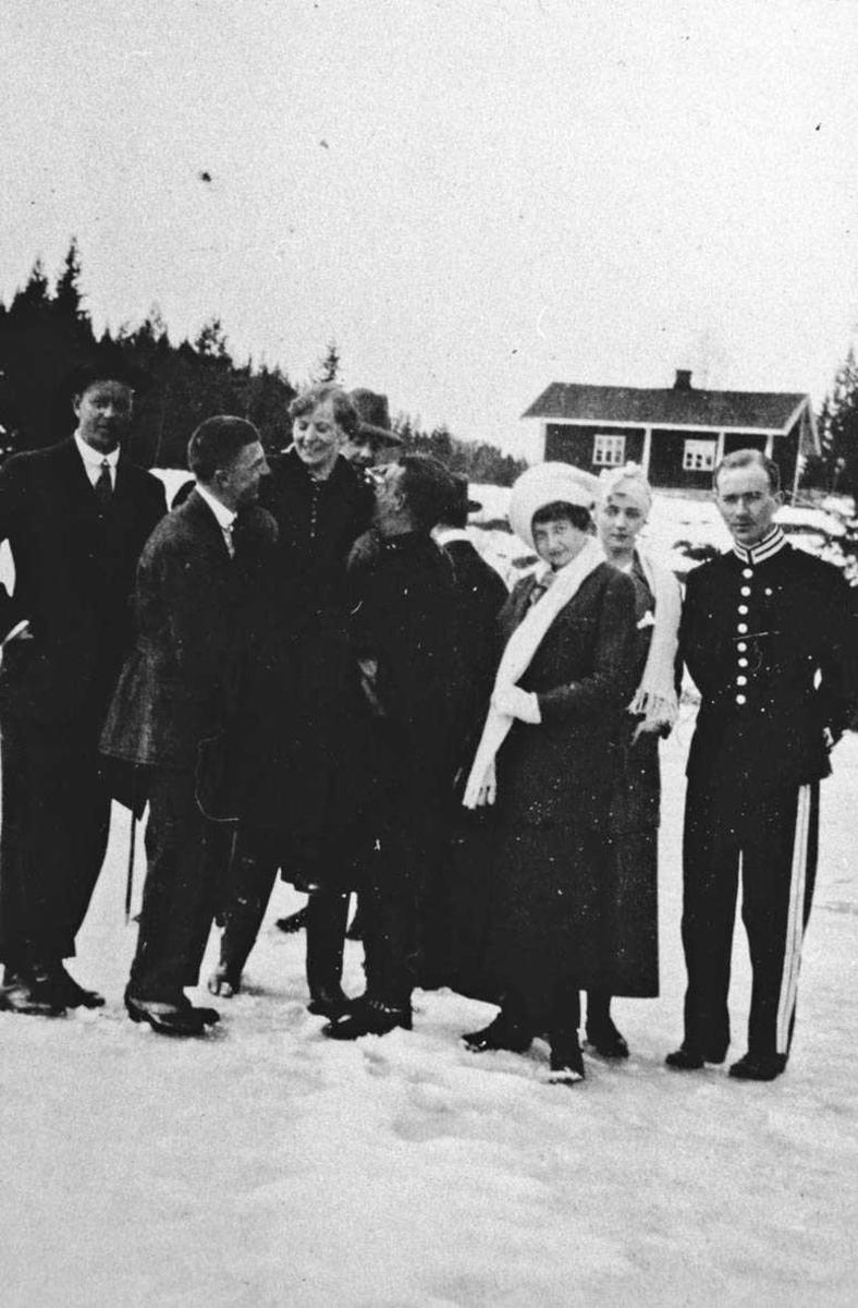 Kvinner og menn, en i uniform samlet ute en vinterdag. Losby.