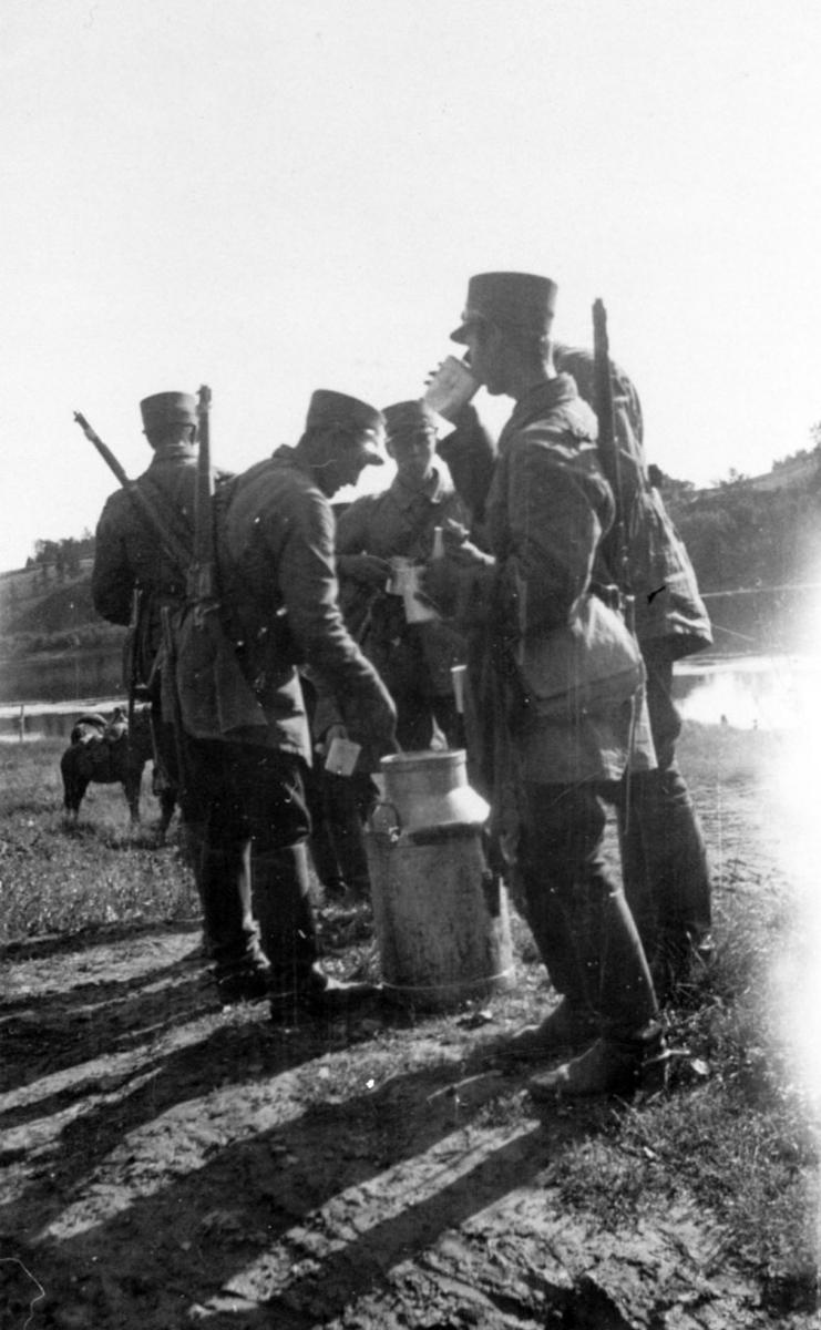 Soldater i rideantrekk.Pause med å drikke melk fra melkespann.