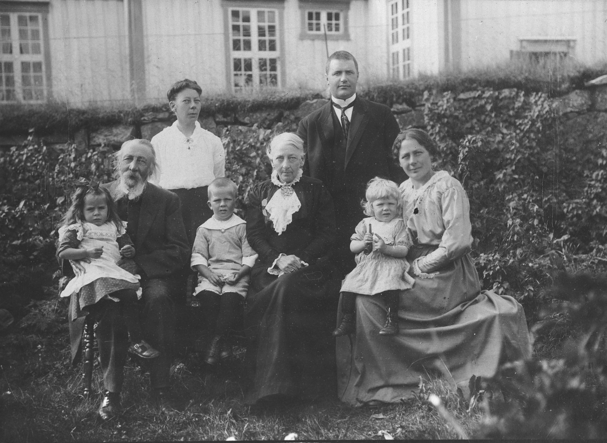 Familegruppe i hagen. Prost August Venaas, kone og døtre