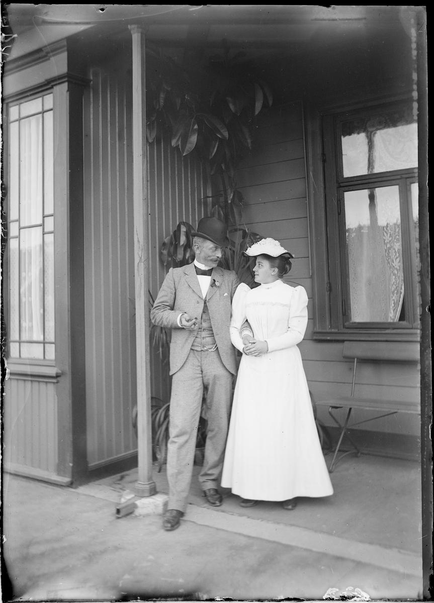 Jens og Elise Frölich (f. Mathiesen) foran en husvegg.