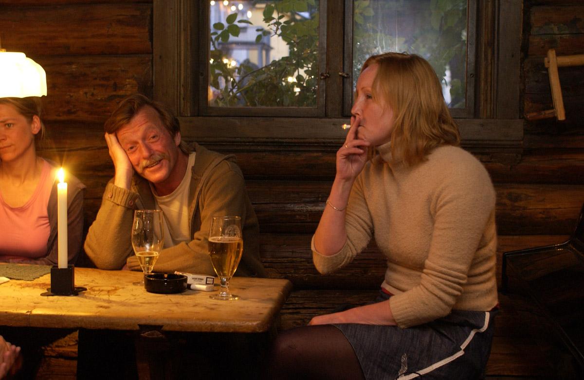 Siste time før røykeloven trer i kraft. Mann og to kvinner ved et gruppebord. På bordet er det sigaretter, øl & askebeger. Det Gamle Bageri Ost & Vinstue.