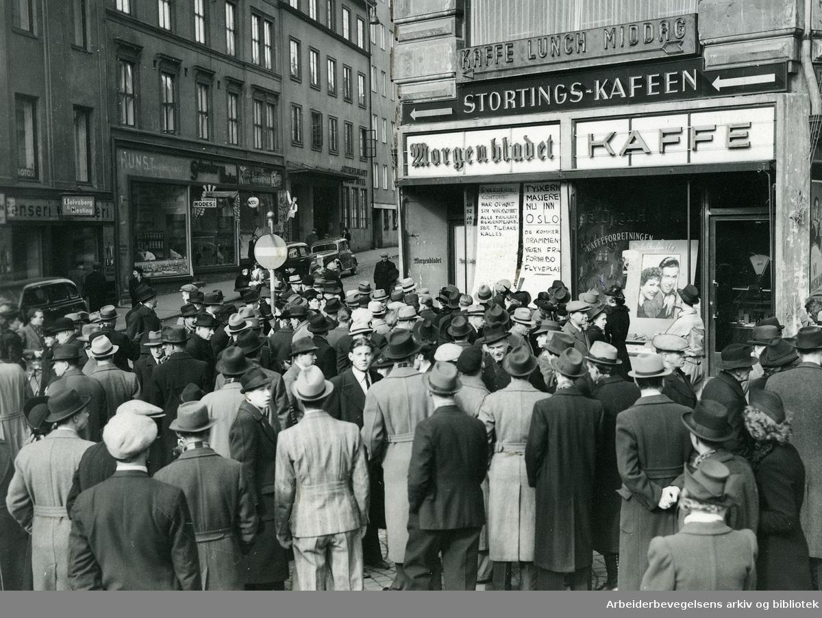 """Morgenen den 9. april 1940 utenfor Morgenbladets ekspedisjon nederst i Lille Grensen. På en plakat i vinduet står det: """"Tyskerne masjerer nu inn i Oslo. De kommer Drammensveien fra Fornebo flyveplass."""" Ved siden av: """" Evakueringskontoret har ophørt sin virksomhet. Alle tidligere bekjentgjørelser tilbakekalles."""""""