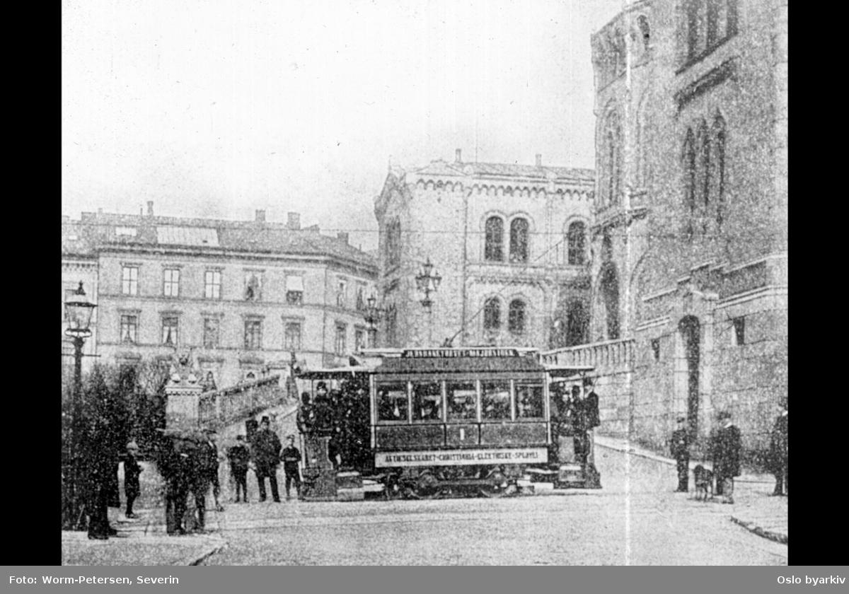 En av AS Kristiania Elektriske Sporveiers (Blåtrikkens) første vogner like etter at driften startet opp i 1894. Trikken hadde 16 sitteplasser og 12 ståplasser. Linje Jernbanetorget-Majorstuen, her ved Stortinget.