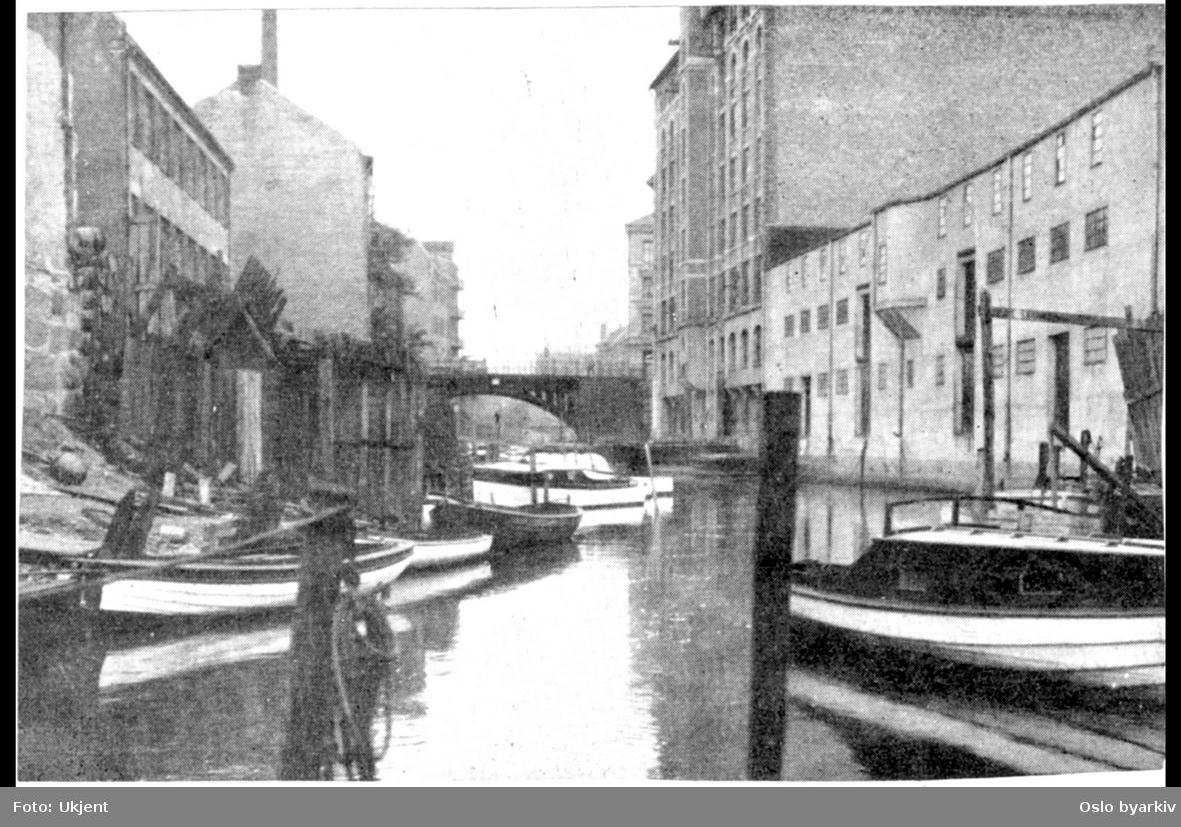 Akerselva mot Vaterlandsbrua med fortøyde båter langs elvas Østre elveløp ved Lakkegata. Småindustri og boliger. Båtfester. Industri og kontorbygg langs vestre bredd i Fjerdingen mellom Hausmannsbrua og Vaterlandsbrua nedenfor Christian Krohgs gate.