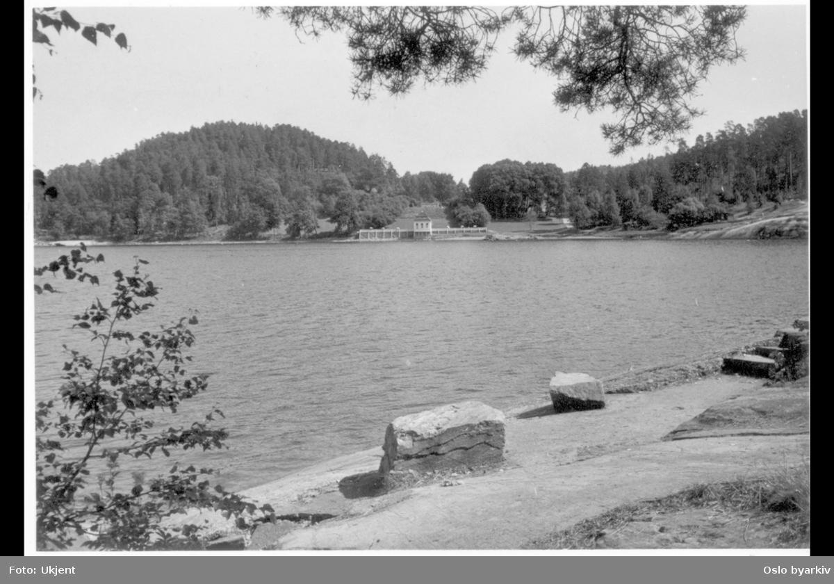 Hvervenbukta sett fra syd mot det tidligere lysthuset (rokokkopaviljongen) til Stubljan gods. Nå kiosk og kafé (uteservering) for badeplassens gjester. (Godsets hovedbygning brant ned i 1913.) Strandpromenade.