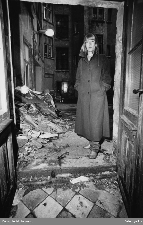 Kvinne utenfor døra mot en forslummet bakgård. Fotografiet er fra prosjektet og boka ''Oslo-bilder. En fotografisk dokumentasjon av bo og leveforhold i 1981 - 82''. Kontakt Samfoto ved ev. bestilling av kopier.