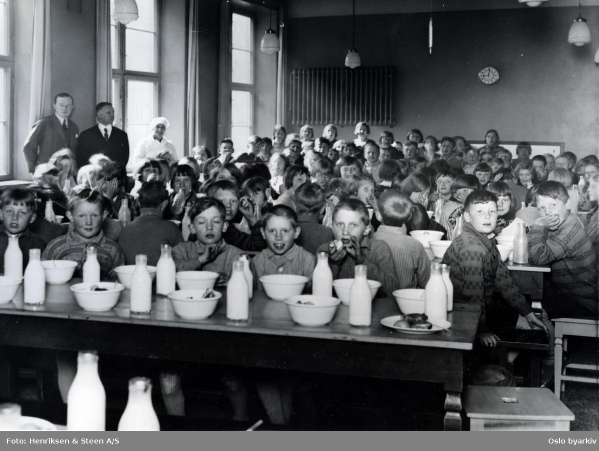 Skolefrokost i matsalen ved Sagene skole. Elevene ved langbord med mat og melkeflasker. Forløper til Oslofrokosten (fast etablert 1932)