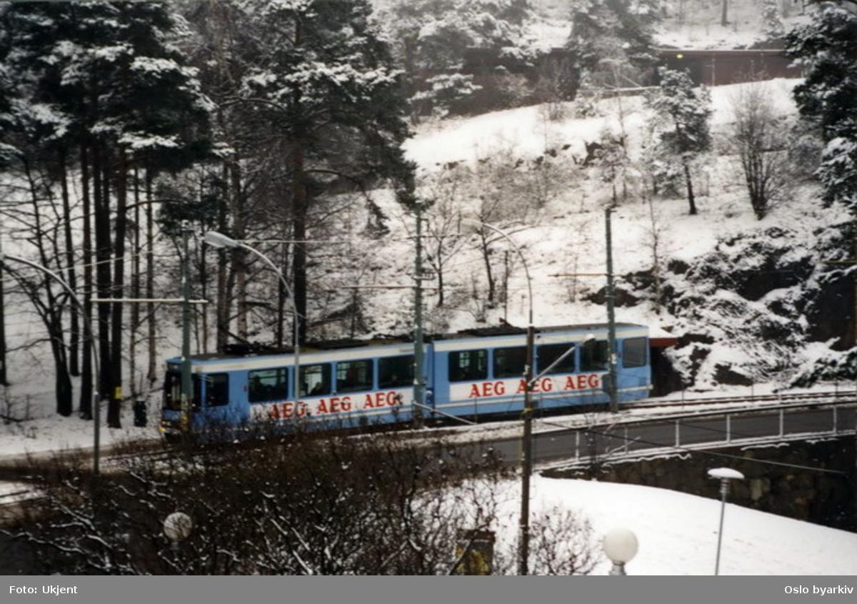 Tyskprodusert leddtrikk på linje 9, Ekebergbanen, på vei nedover langs Kongsveien ved Sjømannsskolen. Ekebergskrenten. Trikkereklame for AEG ( Allgemeine Elektricitäts-Gesellschaft), leverandør av det elektriske anlegget.