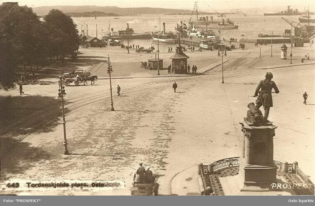 Oslo Sporveier. Tordenskiolds plass. Utsikt over havna (Pipervika), statue av sjøhelten, Nesoddbåter, orlogsfartøy i havna. Den store i bakgrunnen kan være HMS Hood. Prospektkort 443.