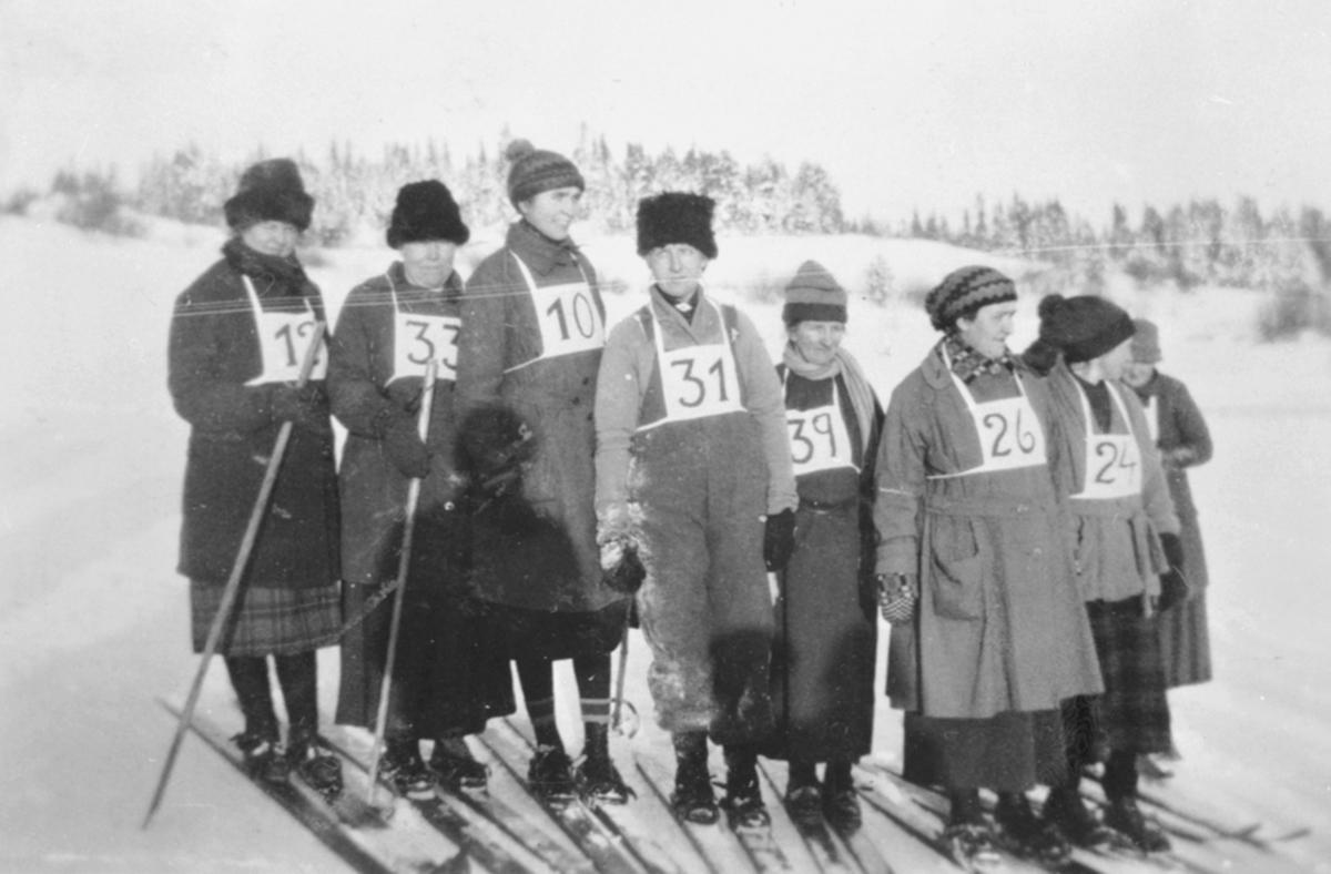 Skiløpere med nummer på brystet. Dameklassen i skirenn i Fredheimbakken, Nes, Hedmark. Fra venstre er Maja Fossum, Karen Borud, Anna Feiring, S. Wilberg med flere.