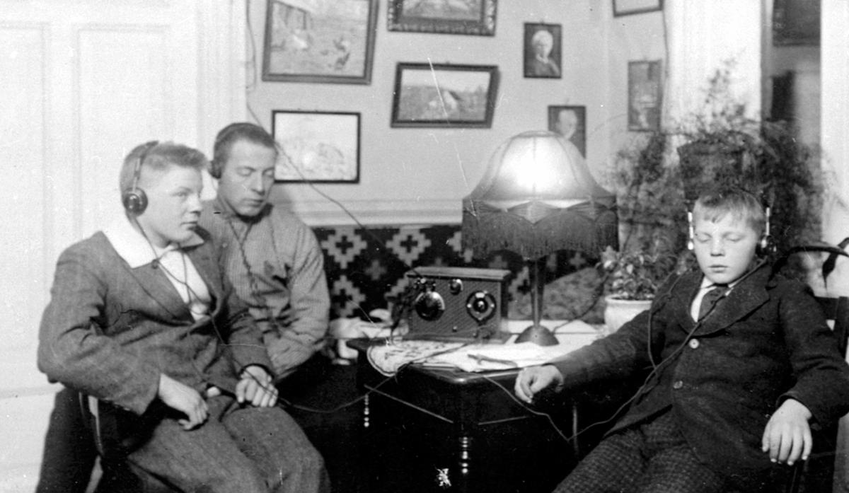 Interiør, stue. Andreas, Kristian og Ole Heramb lytter på radio, krystallapparat, med hodetelefoner. Heramb, Gaupen, Ringsaker.